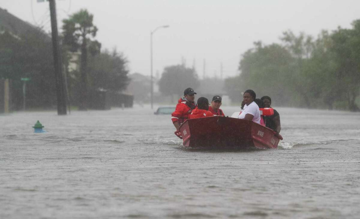 A United States Coat Guard crew from West Virginia rescues people from rising flood waters in a neighborhood along Beechnut Road, south of the Barker Reservoir, as heavy rains continue from Tropical Storm Harvey, Monday August 28, 2017, in Fort Bend County. ( Jon Shapley / Houston Chronicle )