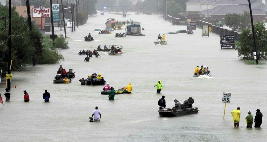 Rescue boats float on a flooded street as people are evacuated in 2017 from rising floodwaters brought on by Hurricane Harvey in Houston. Severe weather in Texas as a result of climate change may have a negative impact on the region's long-term business prospects, economists believe. >>> Click through the gallery to see how a significant sea-level rise would impact cities along the Texas coast.  Photo: David J. Phillip, STF / AP / Copyright 2017 The Associated Press. All rights reserved.