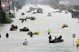 Rescue boats float on a flooded street as people are evacuated in 2017 from rising floodwaters brought on by Tropical Storm Harvey in Houston. Flood recovery funds approved by Congress just months after Hurricane Harvey hit in 2017 will get to Texas in 2020