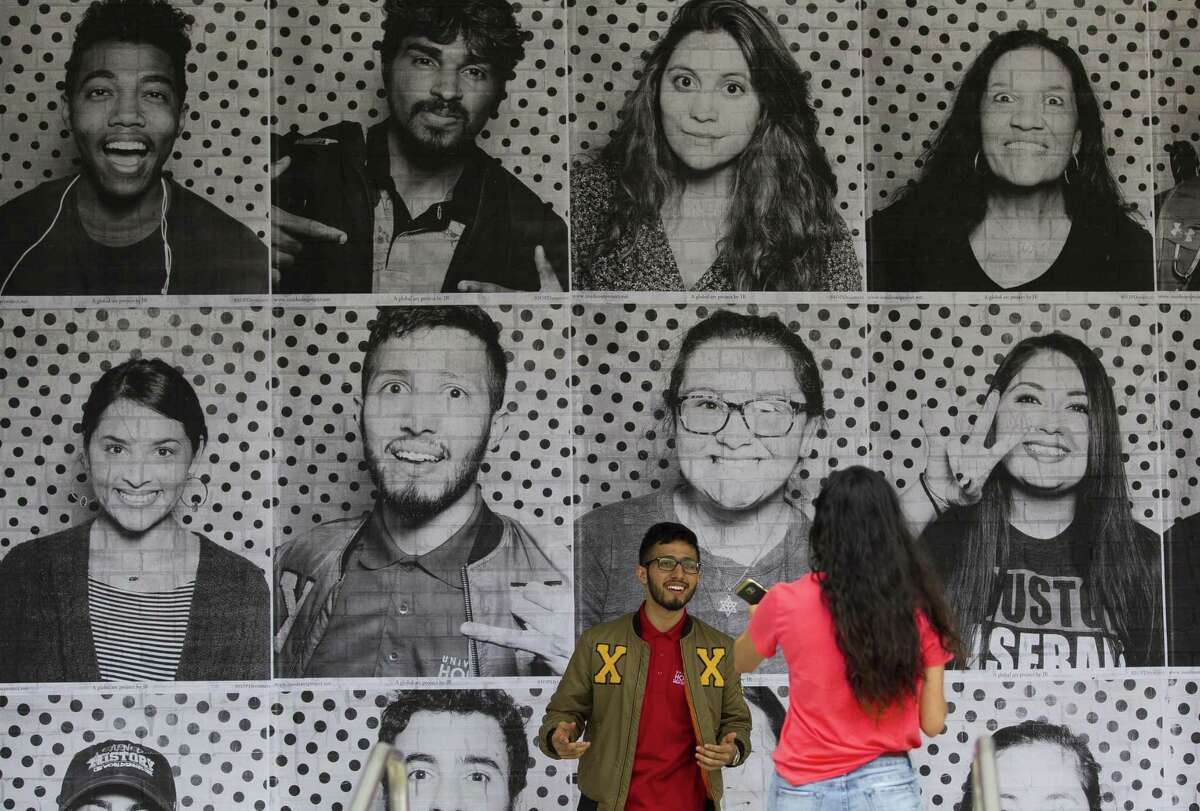 Abraham Garcia, a junior at the University of Houston and a DACA recipient, takes a picture in front of the photo he took earlier as part the Inside Out Dreamers project at the University of Houston, Tuesday, Dec. 5, 2017, in Houston. The exhibit is intended to urge Congress to pass the DREAM act before the end of the year. ( Mark Mulligan / Houston Chronicle )