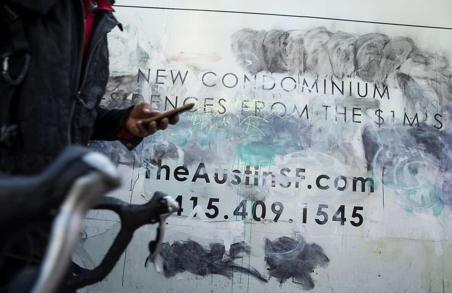 A sign advertising future apartments in the $1 million range is seen graffitied along Market Street Friday, April 13, 2018 in San Francisco, Calif. Photo: Jessica Christian / The Chronicle