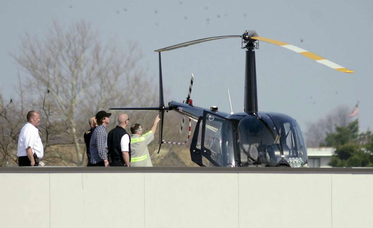 As seen from the offices of Comradity, Stamford police, fire, and city officials meet on the rooftop of a commercial building near Canal and Ludlow streets, where the owner of a light helicopter landed safely on Friday in Stamford. The aircraft had to be lifted off the building by a crane and transported by a flatbed tow to nearby West Beach, where it safely departed in flight over the Long Island Sound.