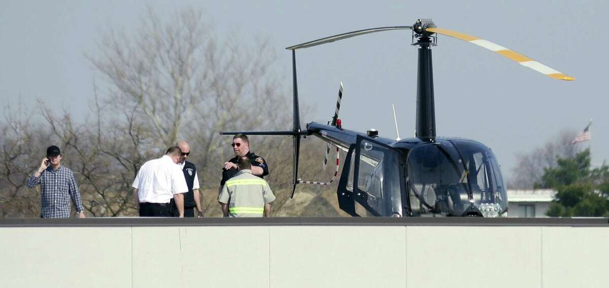 As seen from the offices of Comradity, Stamford Police, Fire, and city officials meet on the roof top of a commercial building near Canal and Ludlow Street, where the owner of a light helicopter landed safely on April 13, 2018 in Stamford, Connecticut. The aircraft had to be lifted off the building by a crane and transported by a flatbed tow to nearby West Beach, where it safely departed in flight over the Long Island Sound.