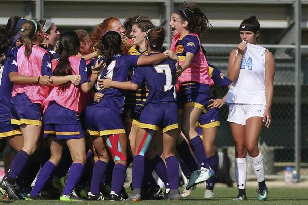 Johnson's Megan Copeland (24) walks past McAllen players celebrating their win over the Jaguars in Region IV-6A high school girls semifinal soccer match at Blossom Field on Friday, Apr. 13, 2018. The Lady Jaguars ended their playoff run against the Lady Bulldogs, 1-2. (Kin Man Hui/San Antonio Express-News)