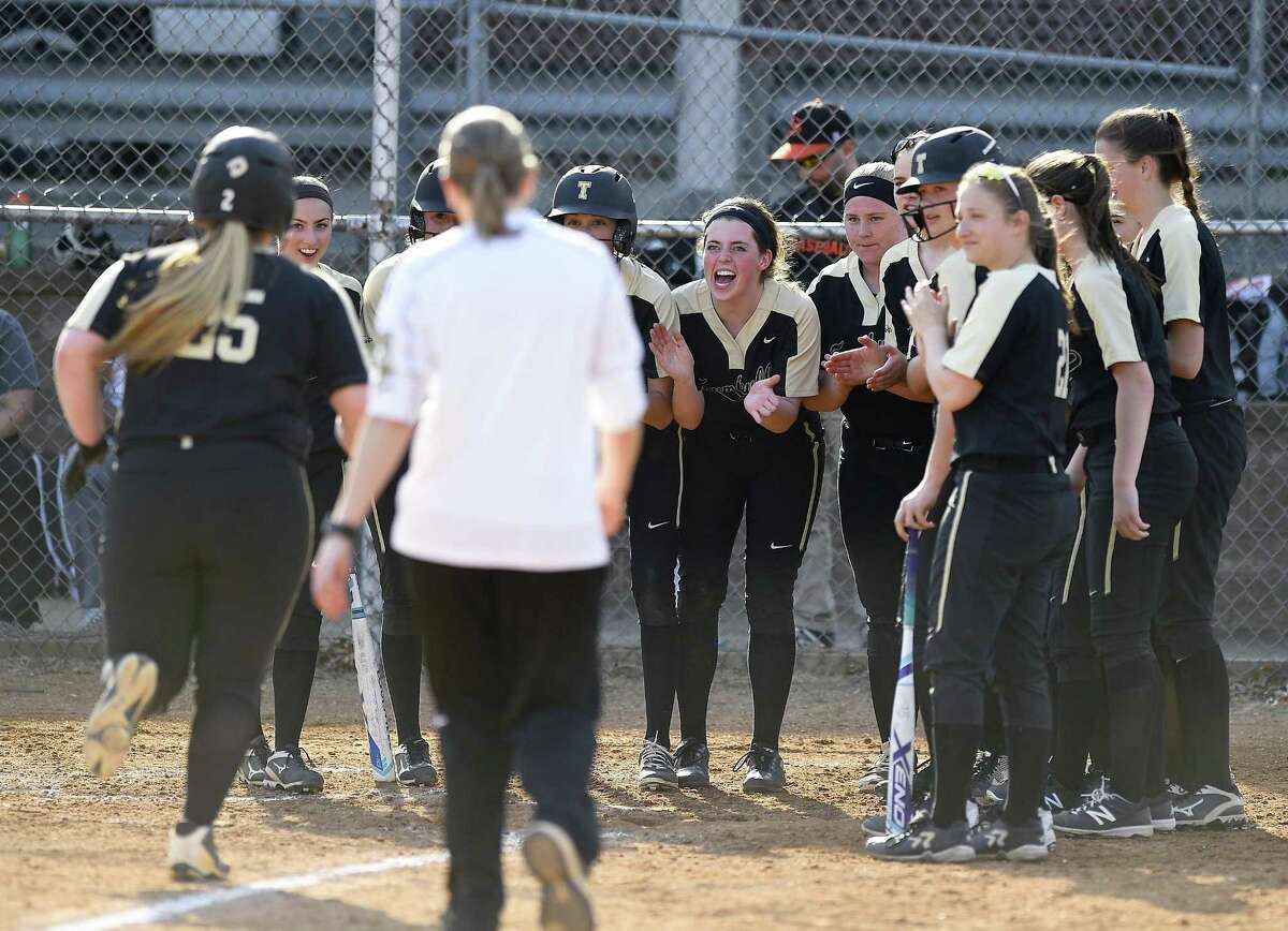 Trumbull's players wait at home plate to celebrate Delilha Destefano (25) a three run homer in the third inning against Stamford at a FCIAC girls softball game at Stamford High School in Stamford, Connecticut on April 13, 2018. Trumbull defeated Stamford 5-1.
