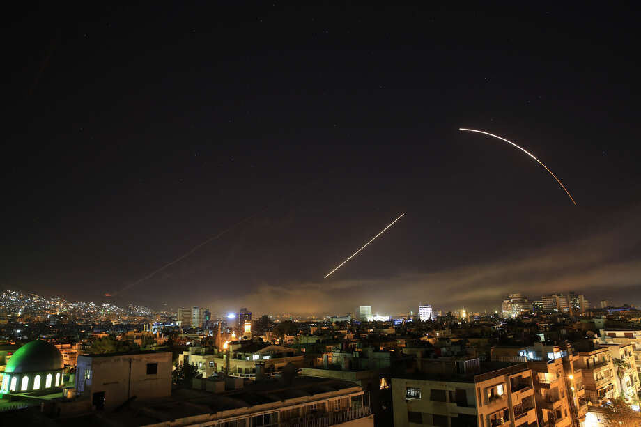 Missiles streak across the Damascus skyline as the U.S. launches an attack on Syria targeting different parts of the capital, early Saturday, April 14, 2018. Syria's capital has been rocked by loud explosions that lit up the sky with heavy smoke as U.S. President Donald Trump announced airstrikes in retaliation for the country's alleged use of chemical weapons. (AP Photo/Hassan Ammar)