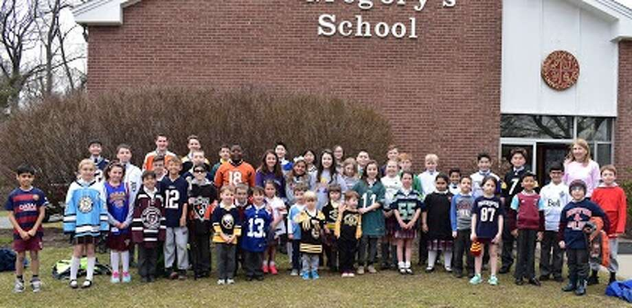 Saint Gregory students wear jerseys over their uniforms Thursday at the Loudonville school to show support for the Humboldt Broncos hockey players of Saskatchewan, Canada, who were on a bus Friday when a semi-trailer slammed in it, killing 15 and injuring 14.