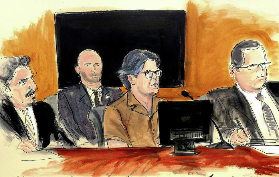 In this courtroom sketch Keith Raniere, second from right, leader of the secretive group NXIVM, attends a court hearing Friday, April 13, 2018, in the Brooklyn borough of New York. Seated, from left, are defense attorney Paul DerOhannesian II, a US marshal, Raniere, and defense attorney Marc Agnifilo. (Elizabeth Williams via AP)