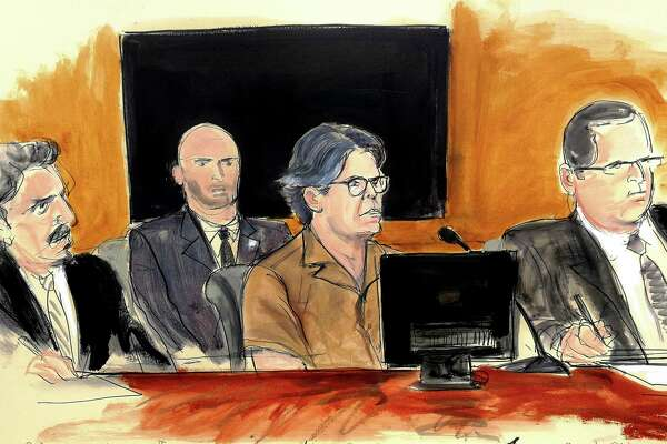 In this courtroom sketch Keith Raniere, second from right, leader of the secretive group NXIVM, attends a court hearing Friday, April 13, 2018, in the Brooklyn borough of New York. In March federal authorities raided an upstate New York residence connected to the group and Raniere, who is accused of coercing female followers into having sex and getting branded with his initials, was later arrested in Mexico where the group also runs programs. Seated, from left, are defense attorney Paul DerOhannesian II, a US marshal, Raniere, and defense attorney Marc Agnifilo. (Elizabeth Williams via AP)