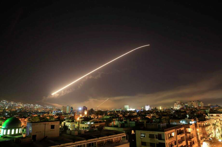 The Damascus sky lights up missile fire as the U.S. launches an attack on Syria targeting different parts of the capital early Saturday, April 14, 2018. Syria's capital has been rocked by loud explosions that lit up the sky with heavy smoke as U.S. President Donald Trump announced airstrikes in retaliation for the country's alleged use of chemical weapons. (AP Photo/Hassan Ammar) Photo: Hassan Ammar / Copyright 2018 The Associated Press. All rights reserved.