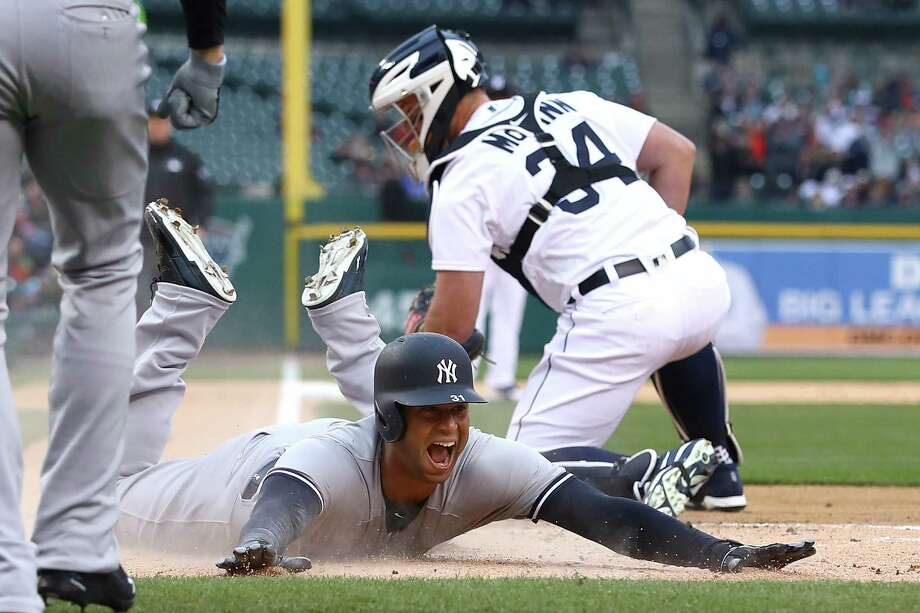 DETROIT, MI - APRIL 13:  Aaron Hicks #31 of the New York Yankees slides into home plate next to James McCann #34 of the Detroit Tigers for a second inning inside the park home run at Comerica Park on April 13, 2018 in Detroit, Michigan.  (Photo by Gregory Shamus/Getty Images) Photo: Gregory Shamus / 2018 Getty Images