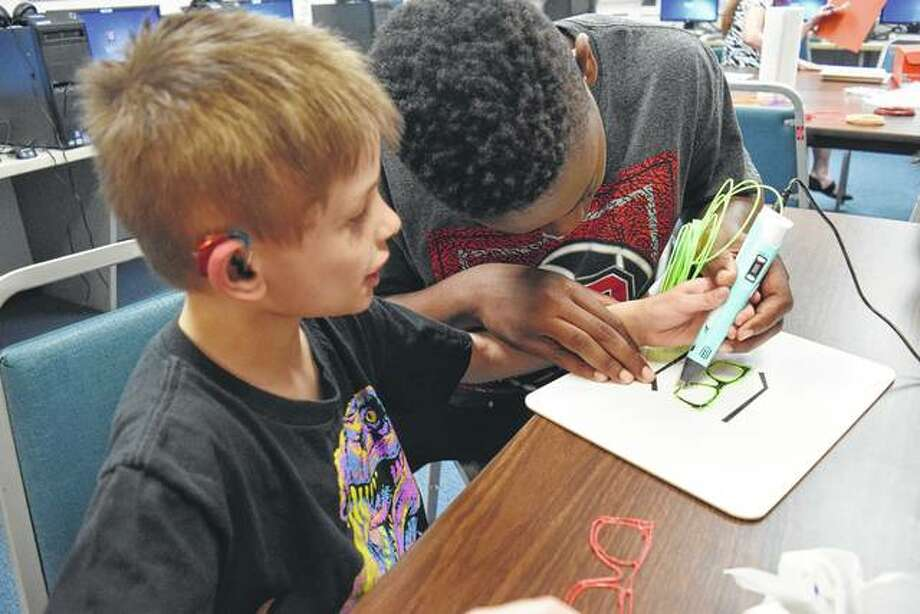 Illinois School for the Deaf kindergartner Mason Hampton of Jacksonville (left) and ISD eighth-grader Joseph Coleman of East St. Louis use a 3-D pen to create 3-D sunglasses Friday at ISD. Photo:       Greg Olson | Journal-Courier