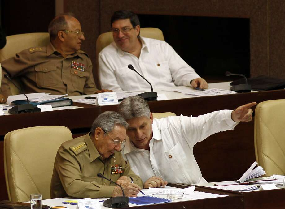 Cuban President Raul Castro (left) confers with Vice President Miguel Diaz-Canel during the opening of a legislative session at Cuba's National Assembly in Havana in 2013. Photo: Ismael Francisco / Associated Press 2013