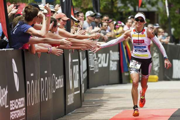 Lisa Roberts slaps hands with fans as she runs to the finish line for third place of the Memorial Hermann Ironman North American Championship Texas triathon in May 2016 in The Woodlands.