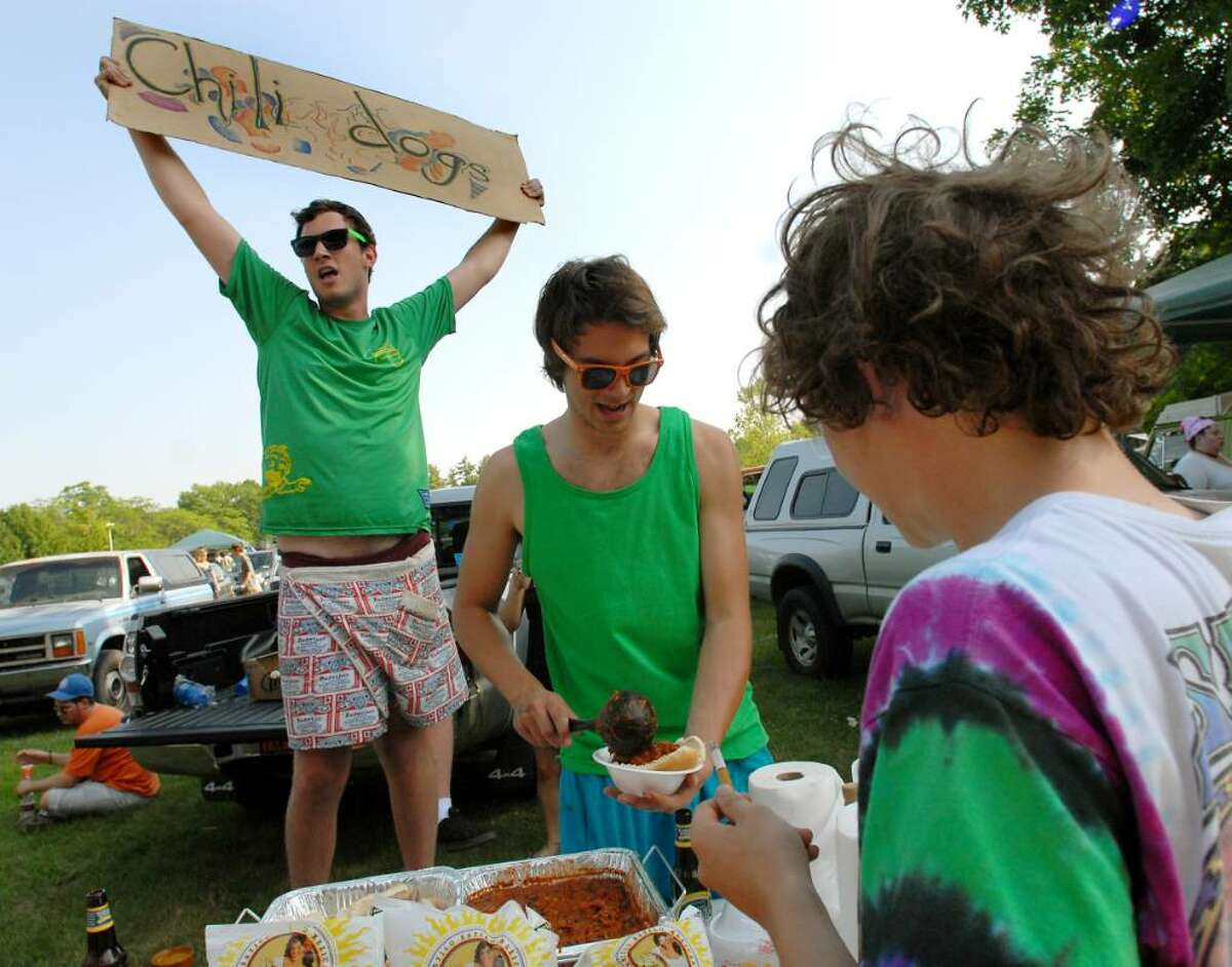 Skidmore College students Andrew Richardson, left, and Scott Cantor, center, sell chili dogs before the Phish show on Saturday at Saratoga Performing Arts Center in Saratoga Springs, N.Y. (Cindy Schultz / Times Union)