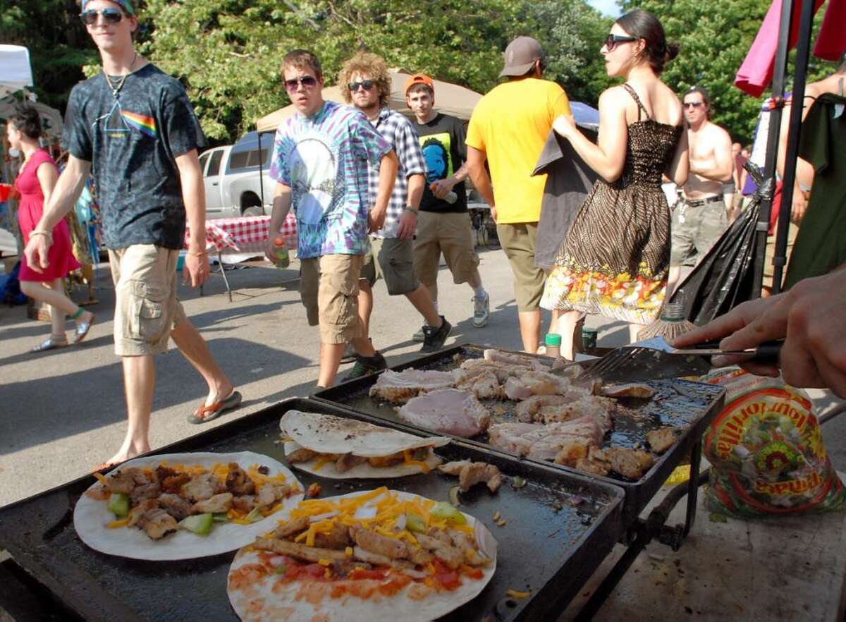 Phish fans walk past a vendor grilling pork quesadillas before the Phish show on Saturday at Saratoga Performing Arts Center in Saratoga Springs. (Cindy Schultz / Times Union)