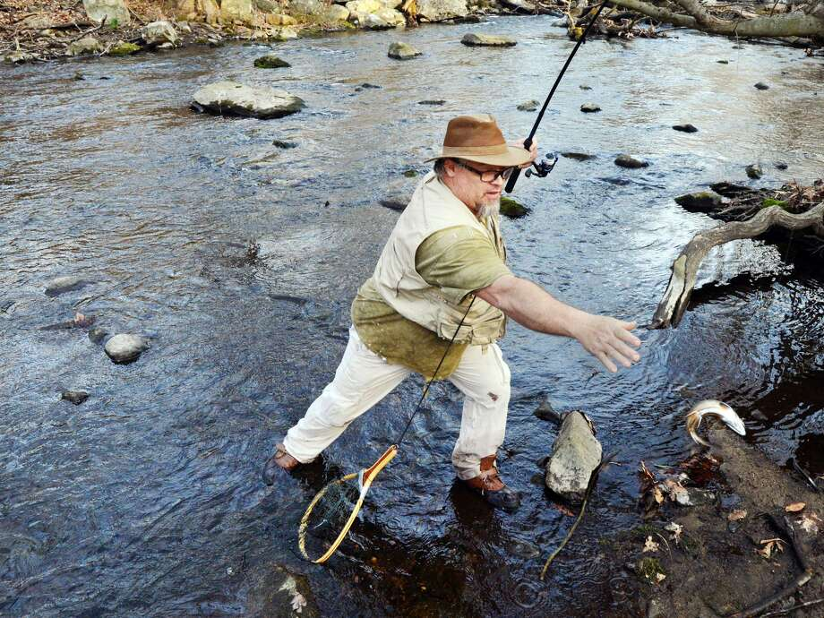 Kevin Jaycox of Stamford reaches for the trout he caught on the opening day of the fishing season on the Mianus River in Greenwich, Conn., Saturday, April 14, 2018. Photo: Bob Luckey Jr. / Hearst Connecticut Media / Greenwich Time