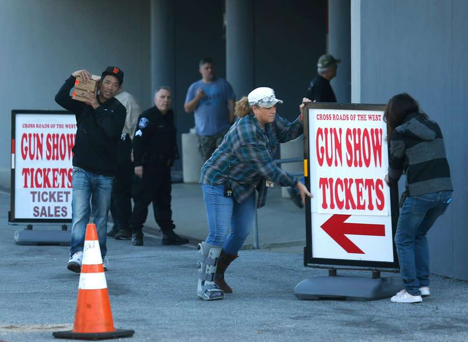 Workers move a sign into place as a man carries boxes of ammunition out of the gun show, which is monitored by police officers. Photo: Photos By Paul Chinn / The Chronicle