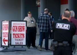At left, a man representing the National Rifle Association offers free admission to the Crossroads of the West gun show for attendees who join the NRA or renew their membership at the Cow Palace in Daly City, Calif. on Saturday, April 14, 2018.