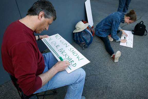 Christopher Gales makes anti-violence protest signs with Johanna Castro outside of the Crossroads of the West gun show at the Cow Palace in Daly City, Calif. on Saturday, April 14, 2018.
