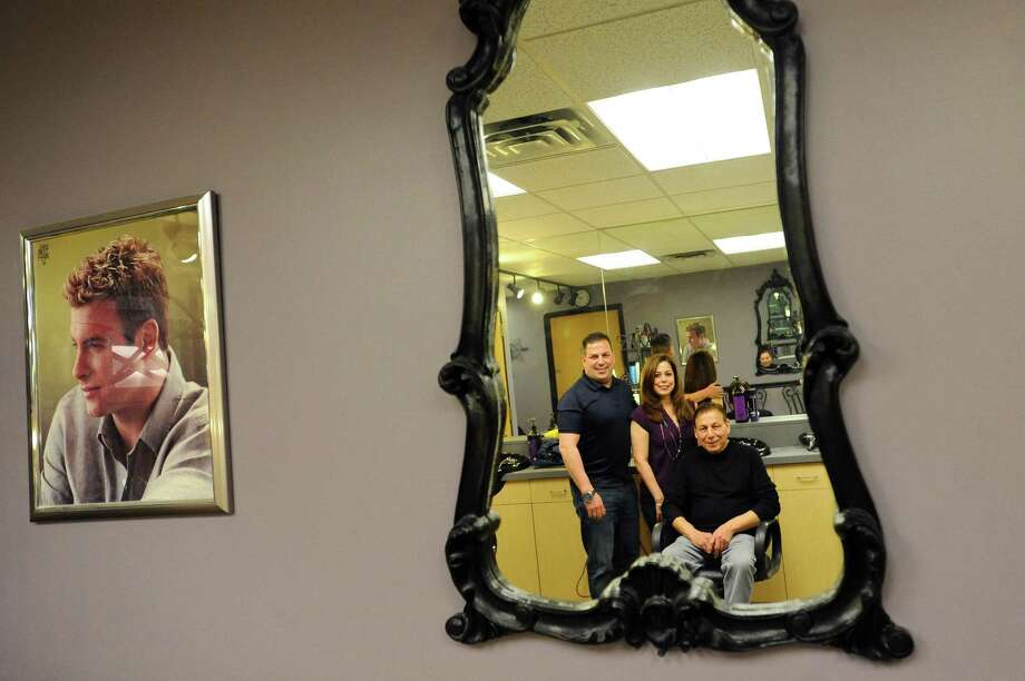 Anthony Rizzi, center, poses for a photo with his children Vinny and Cabrina Rizzi inside Federal Hair Stylists II at the Landmark Building in downtown Stamford, Conn. on Thursday, April 12, 2018. The eldest Rizzi was a member of the first graduating class of J.M. Wright Technical High School in the 1960s and his children followed in his footsteps. Now Anthony's grandson will be a member of the first graduating class of the new and improved Wright Tech, graduating in the spring as a plumber. Photo: Michael Cummo / Hearst Connecticut Media / Stamford Advocate