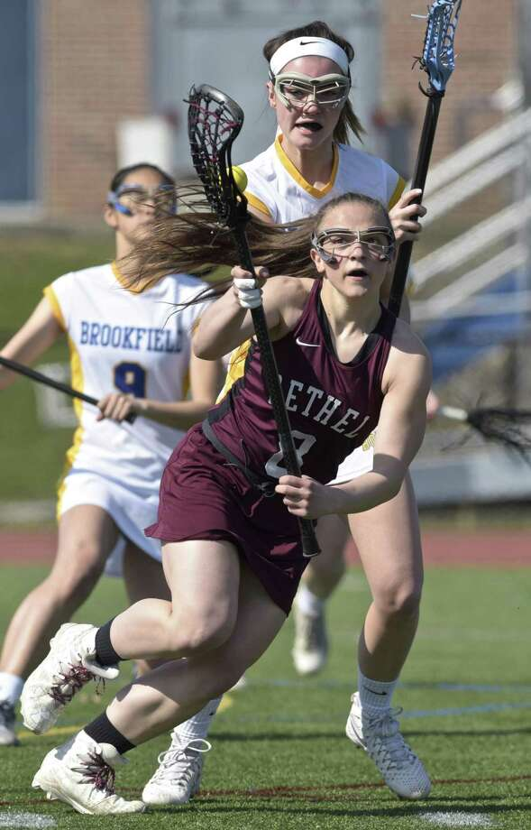 Bethel's Christiana Ruiz (8) moves the ball around Brookfield's Carly Wallin (16) in the girls lacrosse game between Bethel and Brookfield high schools, Saturday morning, April 14, 2018, at Brookfield High School, Brookfield, Conn. Photo: H John Voorhees III / Hearst Connecticut Media / The News-Times