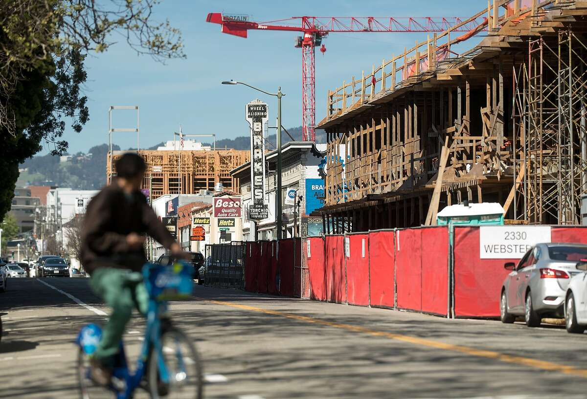 A bicyclist rides down Webster St., where new housing developments rise above decades-old automotive shops, on Friday, April 13, 2018, in Oakland, Calif.