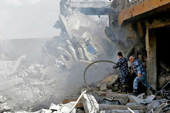 "TOPSHOT - Syrian soldiers inspect the wreckage of a building described as part of the Scientific Studies and Research Centre (SSRC) compound in the Barzeh district, north of Damascus, during a press tour organised by the Syrian information ministry, on April 14, 2018. The United States, Britain and France launched strikes against Syrian President Bashar al-Assad's regime early on April 14 in response to an alleged chemical weapons attack after mulling military action for nearly a week. Syrian state news agency SANA reported several missiles hit a research centre in Barzeh, north of Damascus, ""destroying a building that included scientific labs and a training centre"". / AFP PHOTO / LOUAI BESHARALOUAI BESHARA/AFP/Getty Images"
