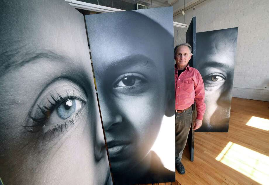 Joe Standart of Lyme is photographed with portraits of immigrants that were part of the New London show, We Are a Nation of Immigrants, at the Urban Collective in New Haven on March 23, 2018. Photo: Arnold Gold / Hearst Connecticut Media / New Haven Register