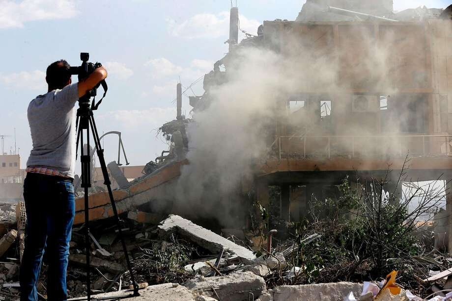 "TOPSHOT - A journalist films the wreckage of a building described as part of the Scientific Studies and Research Centre (SSRC) compound in the Barzeh district, north of Damascus, during a press tour organised by the Syrian information ministry, on April 14, 2018. The United States, Britain and France launched strikes against Syrian President Bashar al-Assad's regime early on April 14 in response to an alleged chemical weapons attack after mulling military action for nearly a week. Syrian state news agency SANA reported several missiles hit a research centre in Barzeh, north of Damascus, ""destroying a building that included scientific labs and a training centre"". / AFP PHOTO / LOUAI BESHARALOUAI BESHARA/AFP/Getty Images Photo: LOUAI BESHARA;Louai Beshara / AFP / Getty Images"