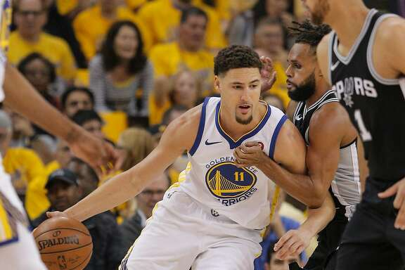 Golden State Warriors' Klay Thompson tries to get around San Antonio Spurs' Patty Mills in the first quarter during game 1 of round 1 of the Western Conference Finals at Oracle Arena on Saturday, April 14, 2018 in Oakland, Calif.