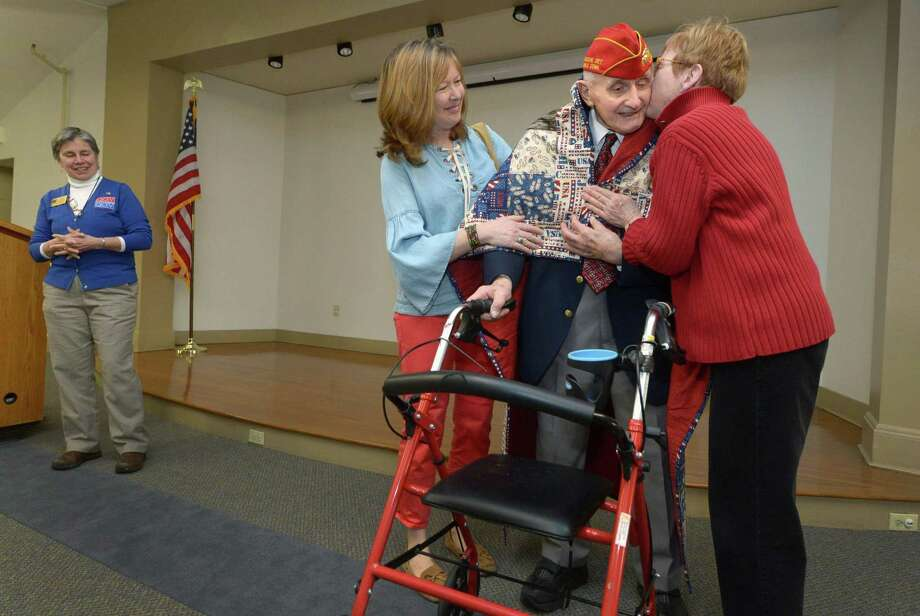 Marine Corps Korean War veteran, Ed Gutkowski, receives his Quilt of Valor and a kiss from quilt makers Brenda Scolaro and Cathy O'Hara while Quilts of Valor CT State Coordinator Jane Dougherty looks on, left, as notable Norwalk veterans are presented with patriotic quilts by Daughters of the American Revolution during a Quilts of Valor ceremony Saturday, April 14, 2018, at the South Norwalk Library in Norwalk, Conn. Photo: Erik Trautmann / Hearst Connecticut Media / Norwalk Hour