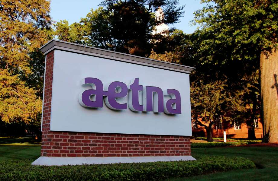 FILE- In this June 1, 2017, file photo, a sign stands on the campus of the Aetna headquarters in Hartford, Conn. Some major health insurers plan to take a little sting out of prescription drug prices by giving customers rebates at the pharmacy counter, and they could spark a trend. Aetna and UnitedHealthcare both say they will begin passing rebates they get from drugmakers along to some of their customers starting next year. (AP Photo/Bill Sikes, File) Photo: Bill Sikes / Copyright 2017 The Associated Press. All rights reserved.