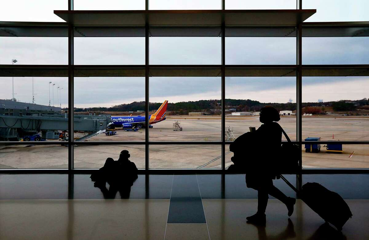 FILE- IN this Dec. 19, 2016, file photo, travelers walk through a the airport to board an airplane during holiday travel at the Birmingham-Shuttlesworth International Airport in Birmingham, Ala. Major airlines including American Airlines, JetBlue, Southwest Airlines and United Airlines integrate buy-now-pay-later concepts into their online booking. (AP Photo/Brynn Anderson, File)