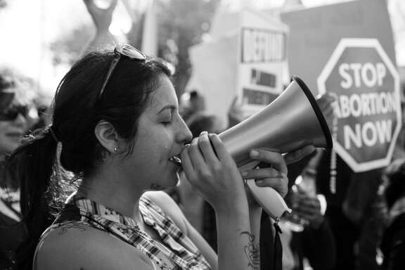 Mercedes Soto cries as she sings a hymn into a megaphone while she and more than a thousand other anti-abortion protestors face off with abortion rights advocates in the intersection in front of the Whole Woman's Health abortion clinic in McAllen, Texas on January 21, 2017.