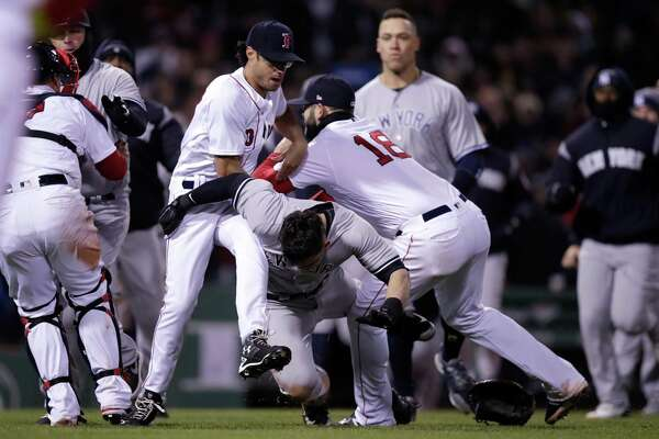 Red Sox pitcher Joe Kelly, left, and first baseman Mitch Moreland, right drop the Yankees' Tyler Austin, center, to the grass during a fight on Wednesday at Fenway Park.