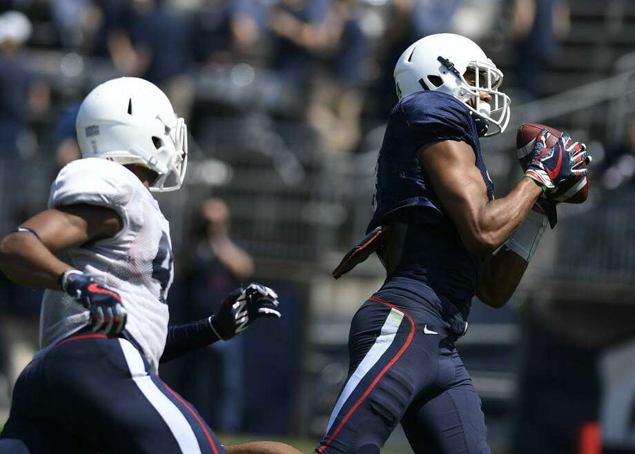 Tight end Aaron McLean, right, catches a pass and runs in for a touchdown as linebacker Marshe Terry pursues during UConn's annual spring game Saturday in East Hartford. Photo: Jessica Hill / Associated Press / AP2018