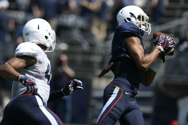 Tight end Aaron McLean, right, catches a pass and runs in for a touchdown as linebacker Marshe Terry pursues during UConn's annual spring game Saturday in East Hartford.