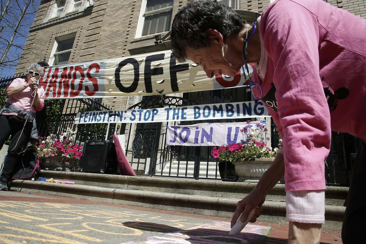 Susan Witka writes Anti-bombing protest messages in front of Senator Dianne Feinstein home on Saturday, April 14, 2018 in San Francisco, CA. Eleanor Levine is at left of a public address speaker.