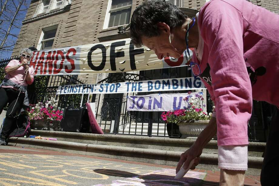 Susan Witka writes Anti-bombing protest messages in front of Senator Dianne Feinstein home on Saturday, April 14, 2018 in San Francisco, CA.  Eleanor Levine is at left of a public address speaker. Photo: Paul Kuroda / Special To The Chronicle