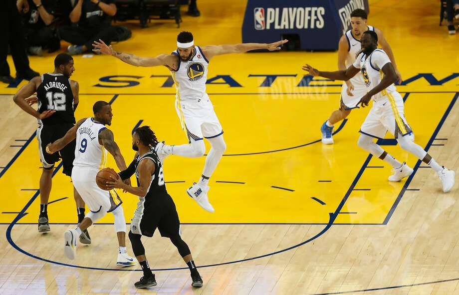 The Warriors' JaVale McGee (center) defends against Spurs guard Patty Mills in the first quarter of a game McGee played defense with tenacity and skill. Photo: Scott Strazzante / The Chronicle