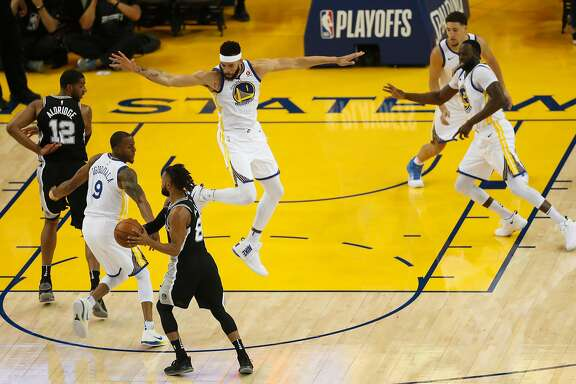 Golden State Warriors' JaVale McGee defends against San Antonio Spurs' Patty Mills in the first quarter during game 1 of round 1 of the Western Conference Finals at Oracle Arena on Saturday, April 14, 2018 in Oakland, Calif.