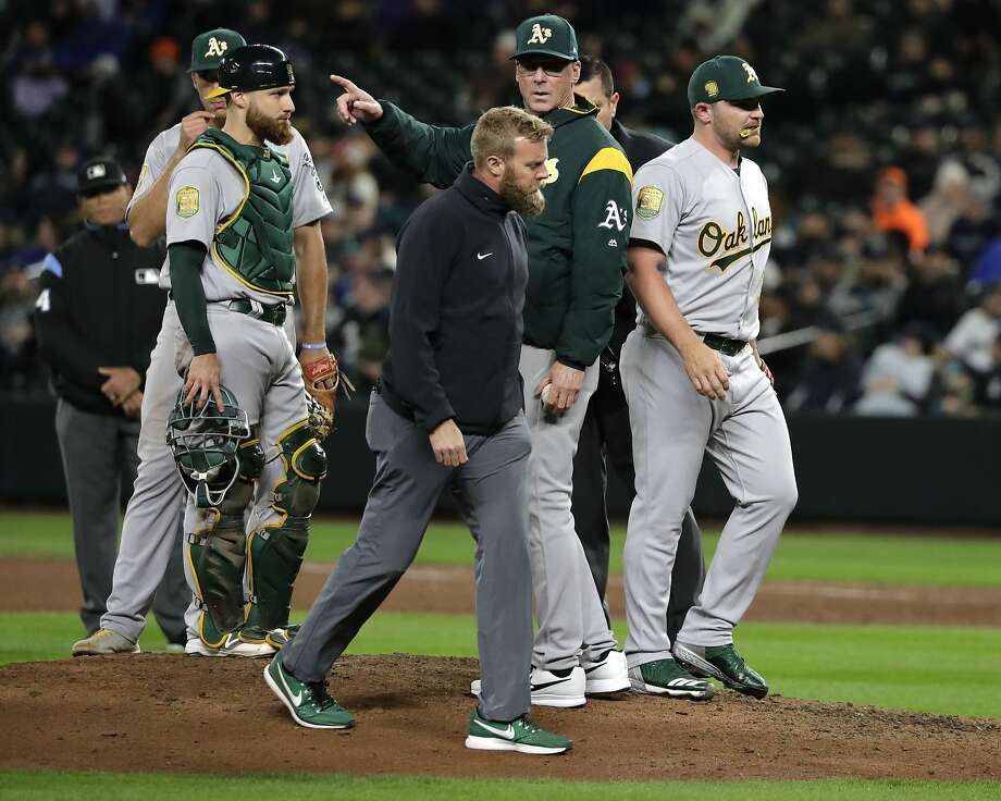 Oakland Athletics manager Bob Melvin, center, signals to the bullpen as pitcher Liam Hendriks, right, leaves the mound with an injury during the eighth inning of the team's baseball game against the Seattle Mariners, Friday, April 13, 2018, in Seattle. (AP Photo/Ted S. Warren) Photo: Ted S. Warren / Associated Press