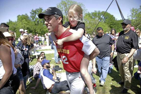 Beto O'Rourke carries his daughter Molly through the crowd as he plays baseball with his old team Los Diablitos at a fundraiser for his campaign for U.S. Senate on April 14, 2018.