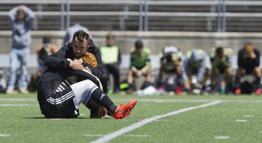 Conroe assistant coach Christian Boehm comforts defenseman Danny Mejia after losing to Coppell 1-0 in the Region II-6A regional finals at the Kelly Reeves Athletic Complex, Saturday, April 14, 2018, in Round Rock. Photo: Jason Fochtman/Houston Chronicle