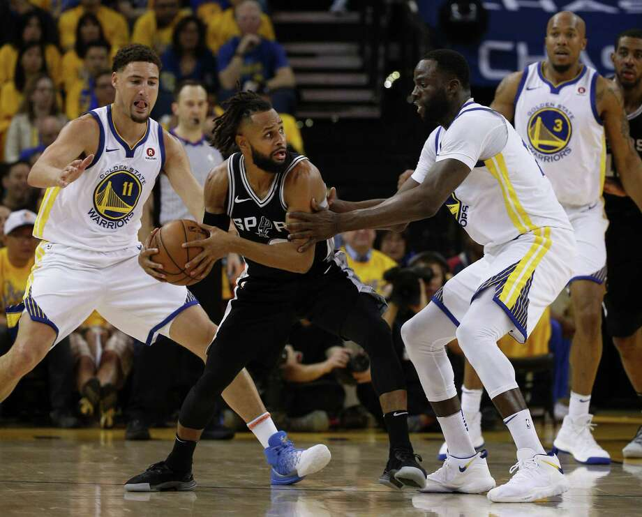 San Antonio Spurs guard Patty Mills (8) is guarded by Golden State Warriors forward Draymond Green (23) during the second quarter of Round 1 Game 1 of the NBA Western Conference Finals between the Spurs and Golden State Warriors at Oracle Arena, Saturday, April 14, 2018, in Oakland, Calif. Photo: Santiago Mejia, Staff / The Chronicle / ONLINE_YES
