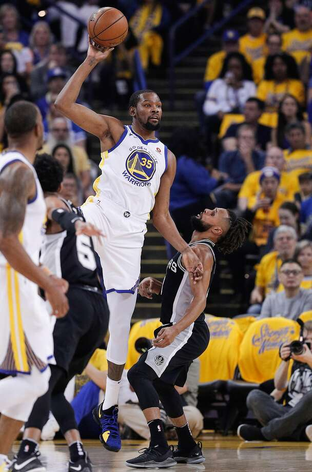 Golden State Warriors' Kevin Durant looks to pass off over San Antonio Spurs' Patty Mills in the second quarter during game 1 of round 1 of the Western Conference Finals at Oracle Arena on Saturday, April 14, 2018 in Oakland, Calif. Photo: Carlos Avila Gonzalez, The Chronicle