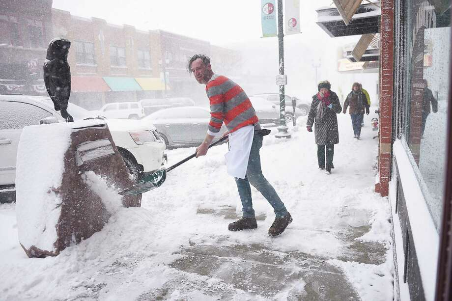 M.B. Haskett cook Mark Romanowski shovels snow in front of the restaurant, Saturday, April 14, in Sioux Falls, S.D. M.B. Haskett was one of the few restaurants open downtown Saturday.   (Briana Sanchez /The Argus Leader via AP) Photo: Briana Sanchez / ©Argus Leader