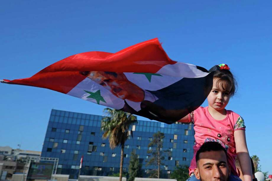 A Syrian girl holds up a Syrian national flag with a picture of President Bashar Assad as government supporters chant slogans against U.S. President Trump during demonstrations following a wave of U.S., British and French military strikes to punish Assad for suspected chemical attack against civilians, in Damascus, Syria, Saturday, April 14, 2018. Hundreds of Syrians are demonstrating in the landmark square in the Syrian capital, waving victory signs and honking their car horns in a show of defiance. (AP Photo/Hassan Ammar) Photo: Hassan Ammar / Copyright 2018 The Associated Press. All rights reserved.