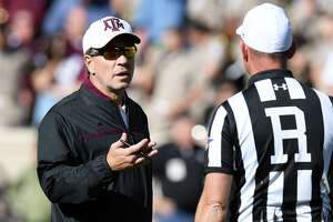 Texas A&M head football coach Jimbo Fisher, left, speaks with an official during the first half of Saturday's Maroon & White game at Kyle Field.